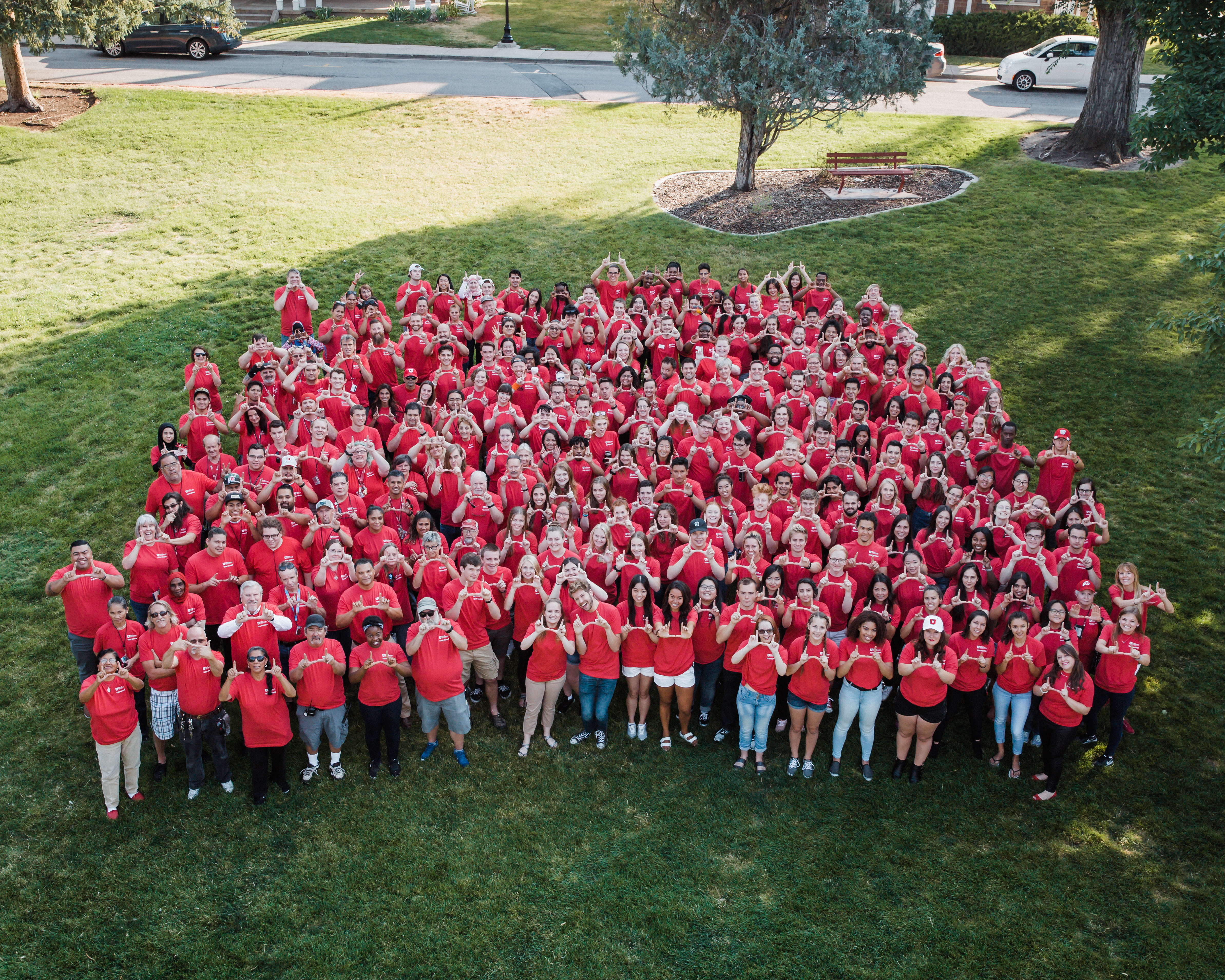 "All staff photo 2018. People wearing red t-shirts standing up in multiple rows on grass. Shot is an ariel view of people holding their hands in ""U"" shape."