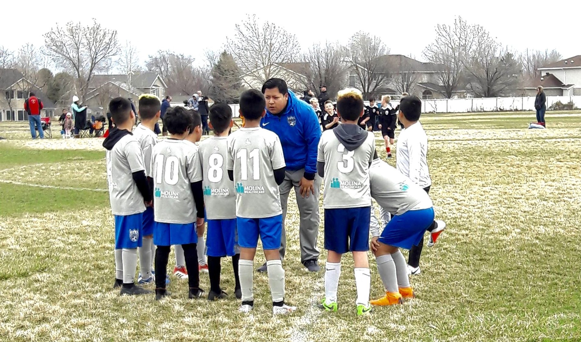 Coach talking to young soccer players on field